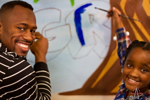 Vernon Davis works on an art project with a youngster.